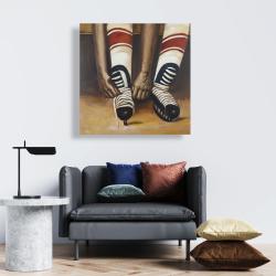 Toile 24 x 24 - Un joueur de hockey attachant ses patins