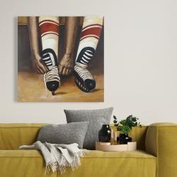 Toile 36 x 36 - Un joueur de hockey attachant ses patins